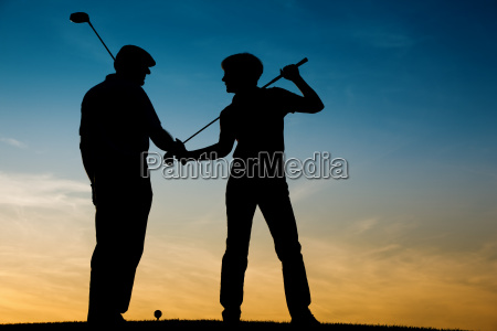 mature couple playing golf in sunset