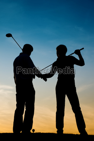 elderly couple playing golf in the