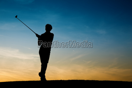 senior golfer silhouetted