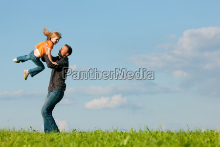 father and daughter on meadow in