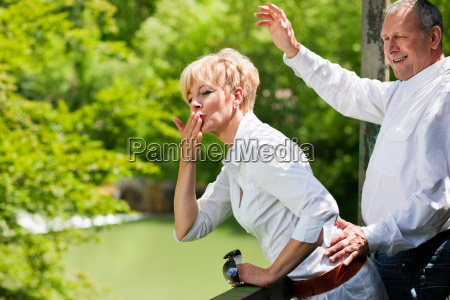 elderly couple on bridge waving