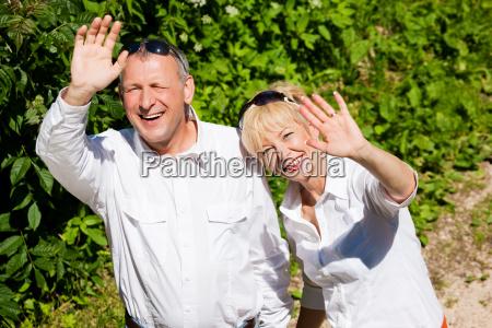 happy elderly couple waving