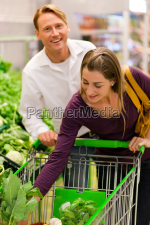 people in the supermarket buy vegetables
