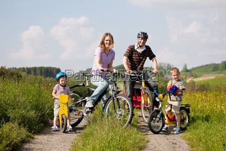family riding bikes in summer