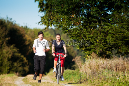 sport couple jogging and riding bikes
