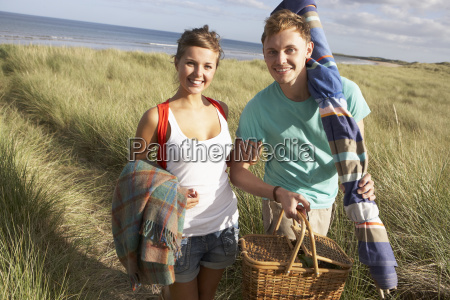 young couple carrying picnic basket and