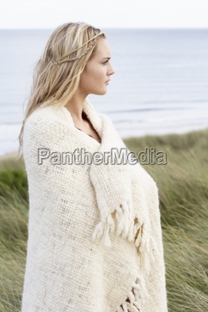 young woman standing in sand dunes