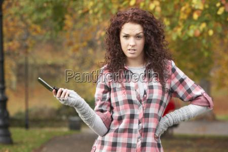 frustrated teenage girl making mobile phone
