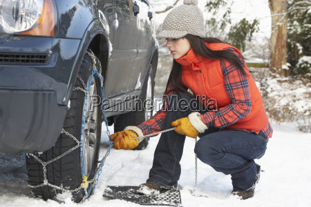 woman putting snow chains onto tyre