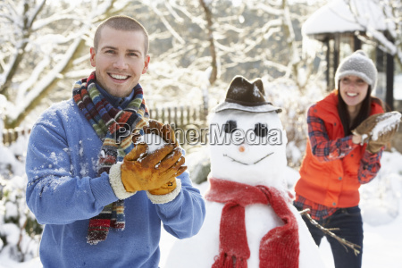 young couple having snowball fight in