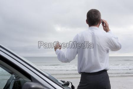 geschaefsmann phone on the beach