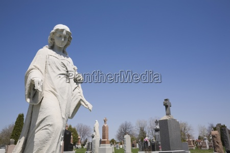 statue and headstones in cemetery laval