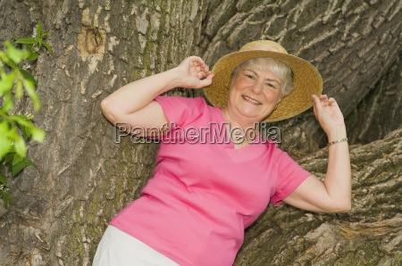 senior woman leaning against a tree