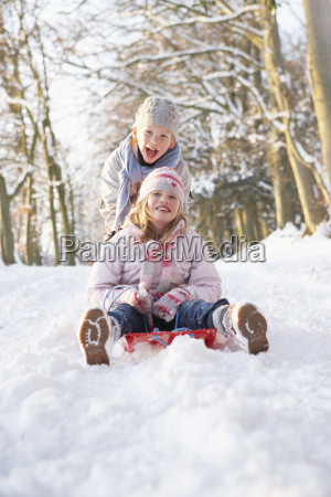boy and girl sledging through snowy