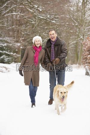 senior couple walking dog through snowy