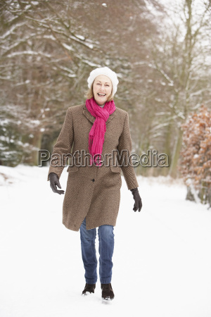 senior woman walking through snowy woodland