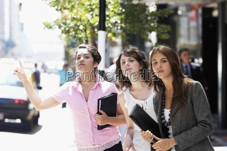 three businesswomen hailing a taxi at