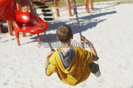 rear view of a boy swinging