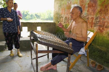 senior man playing hammered dulcimer with