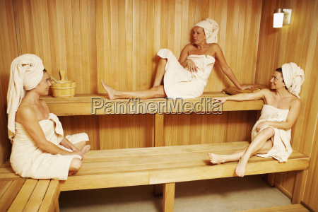 three mature women wearing towels sitting