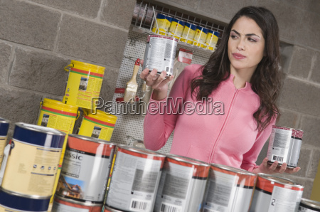 woman holding paint cans in a