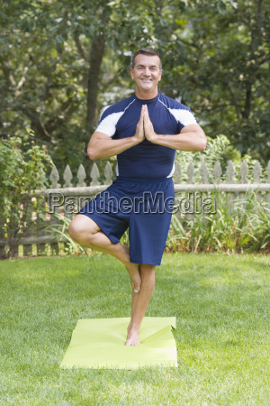 mature man practicing yoga in a