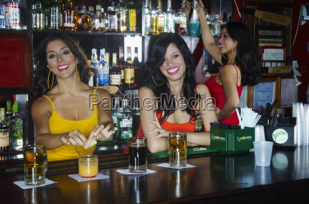 three sexy young waitresses serve drinks