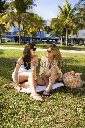 two women sitting on blanket on