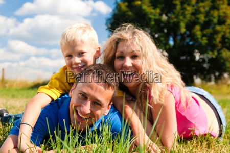 family lies on the grass