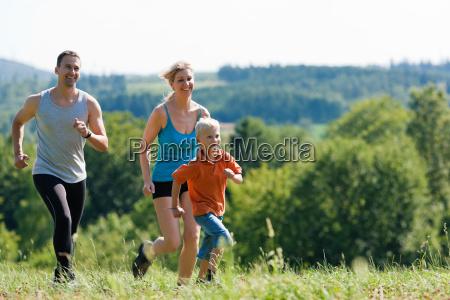 family running through a meadow