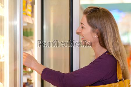 woman in supermarket frozen department