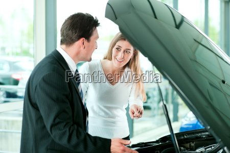 woman buying car in car dealership