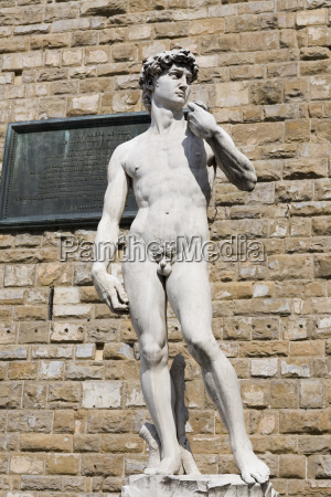 statue in front of a brick