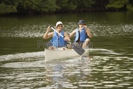 two mid adult men canoeing