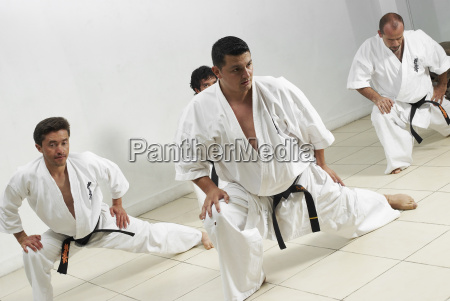 four mid adult men practicing karate