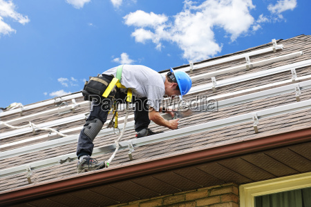 man working on roof installing rails