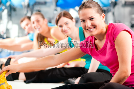 group in fitness studio while warming