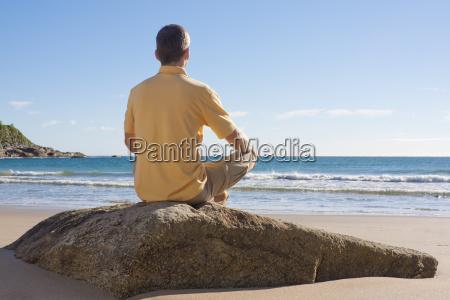 man meditates on the beach