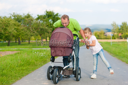 father with child and baby buggy