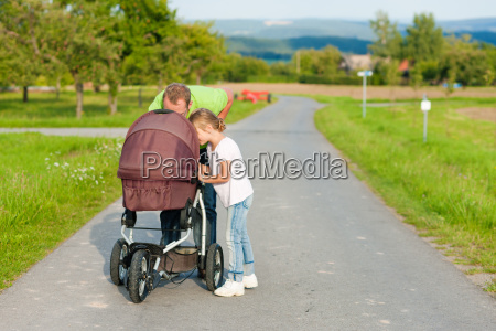 father with child and baby carriage