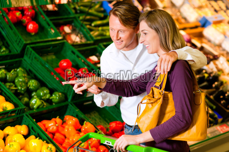 couple in supermarket buying vegetables