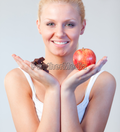 friendly woman holding chocolate and apple