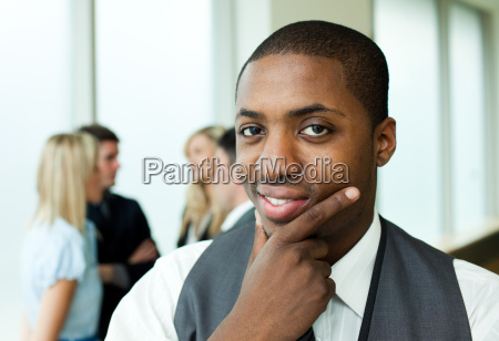 thoughtful ethnic businessman smiling at the