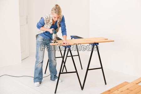 home improvement handywoman cutting wooden