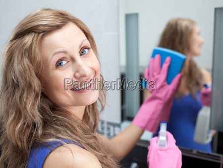 charming woman cleaning a bathrooms mirror