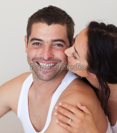 pretty woman kissing her cheerful husband