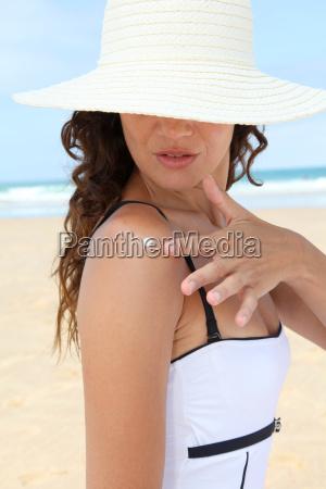 beautiful woman at the beach putting