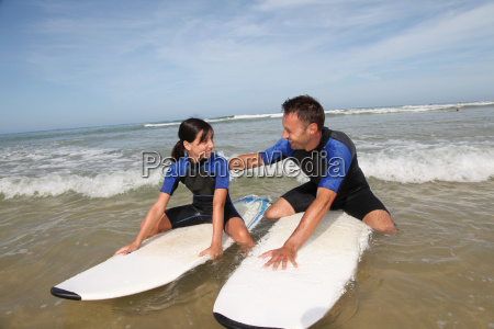 father and daughter surfing in the