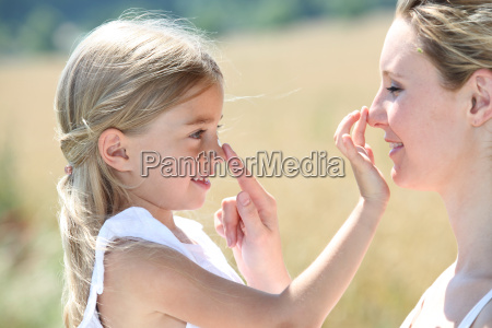 mother and daughter putting sun protection