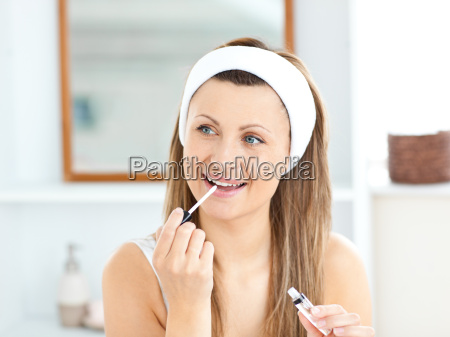 happy woman applying gloss on her